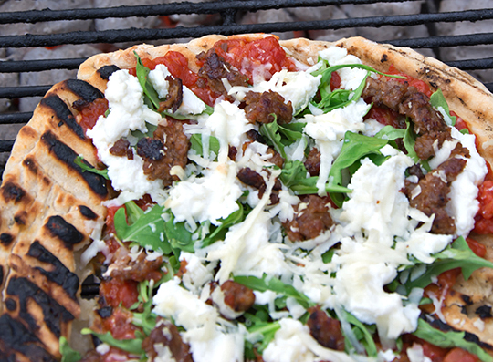 Grilled Pizza With Red Sauce, Sausage and Arugula